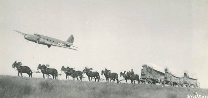 Photo of airplane flying over a wagon train