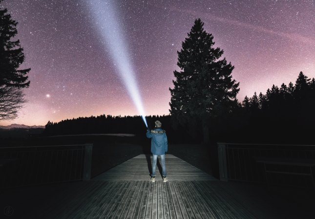 Photo of man shining a flashlight into the night sky