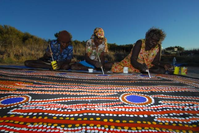 Photo of 3 women working on a collaborative painting