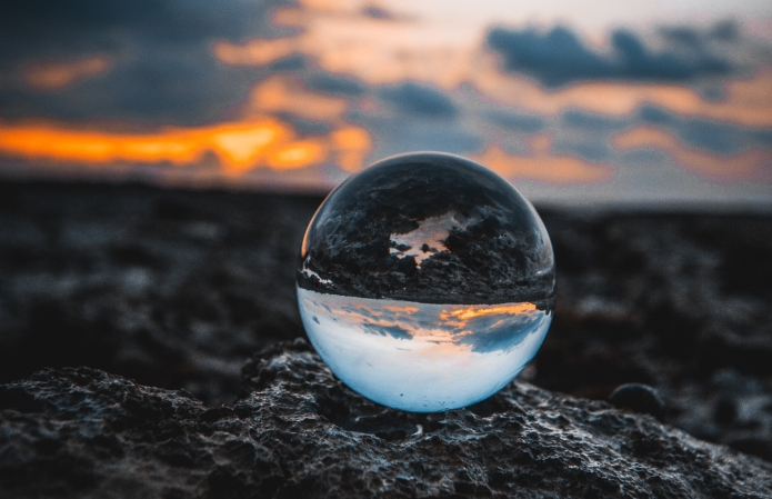 Photo of glass globe in sunset landscape