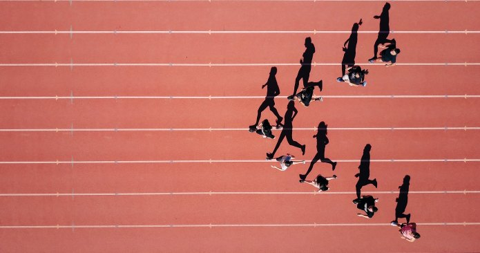 Runners on a track, seen from above, with shadows beside them