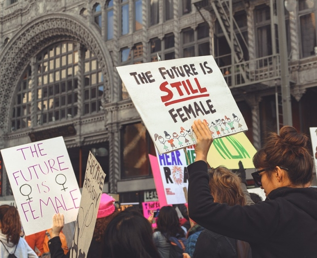 "Photo of protest march with sign reading ""The Future is Still Female"""